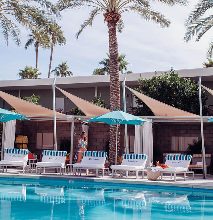 泳池旁边的躺椅由米色窗帘帆和亮青色雨伞遮阴,该窗帘帆由 Sunbrella Contour 面料制成。