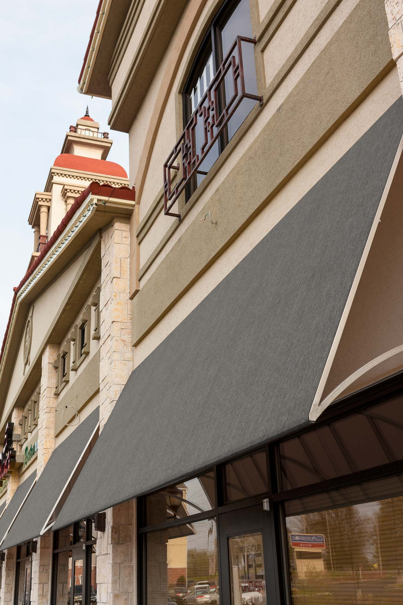 一排商店的侧面俯拍照片,商店橱窗的遮阳篷都采用 Sunbrella SeaMark 织物制成。