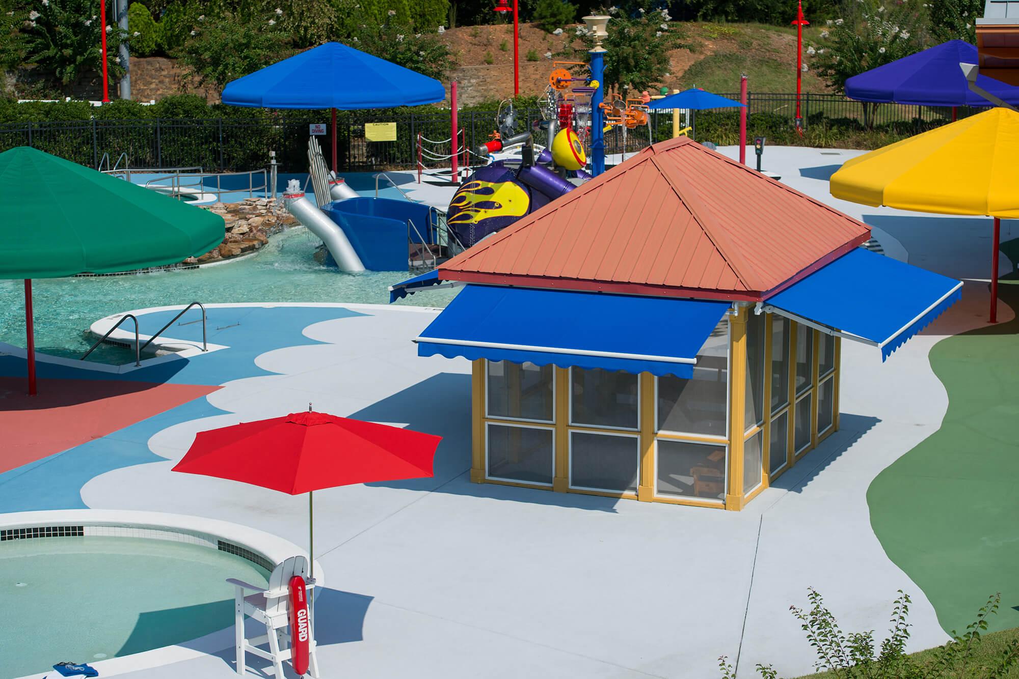带颜色的雨伞和深蓝色的可伸缩遮阳蓬为水上公园遮阴