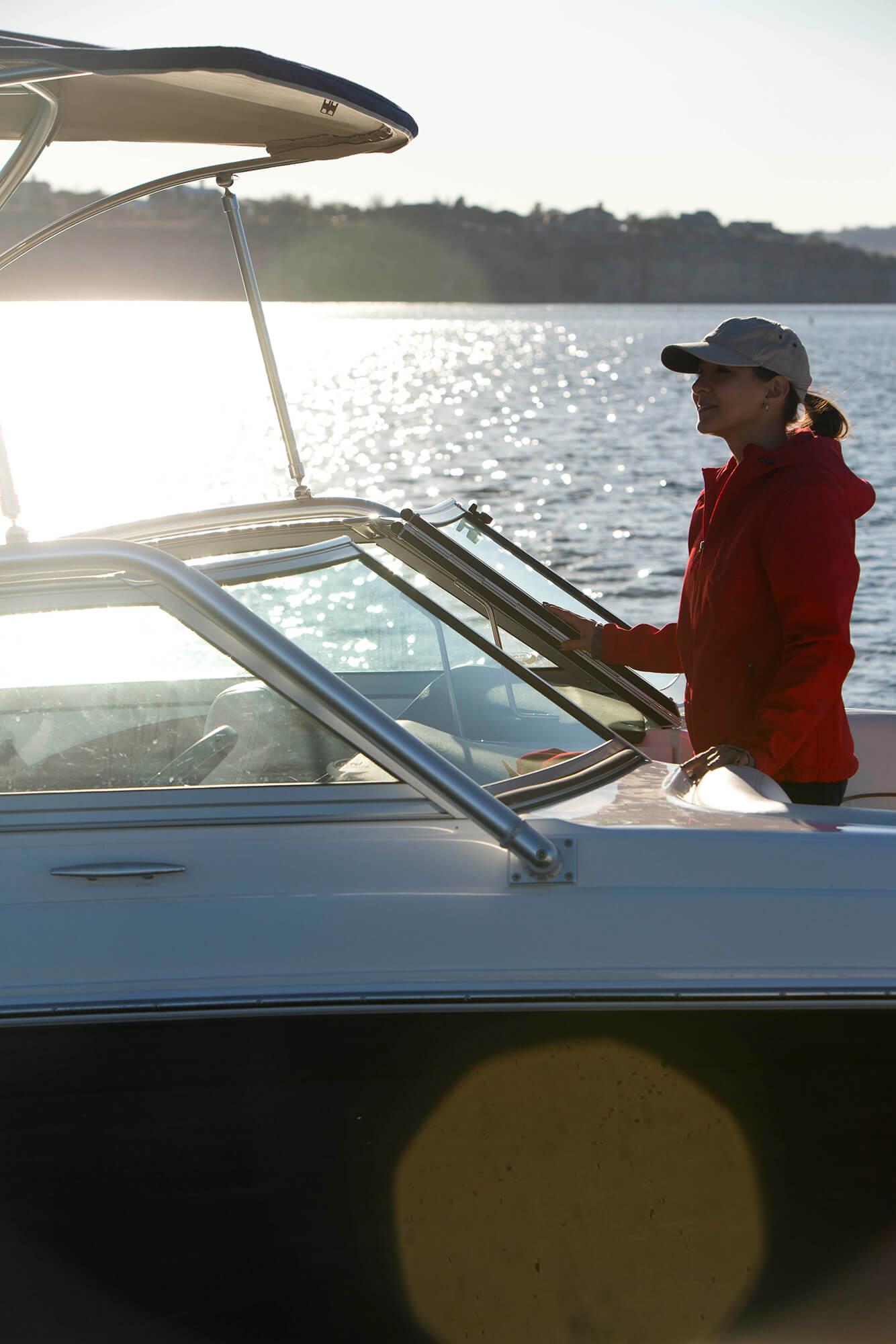 带有由海蓝色 Sunbrella Supreme 织物制成的遮阳蓬的汽艇前方,女人在汽艇船首。