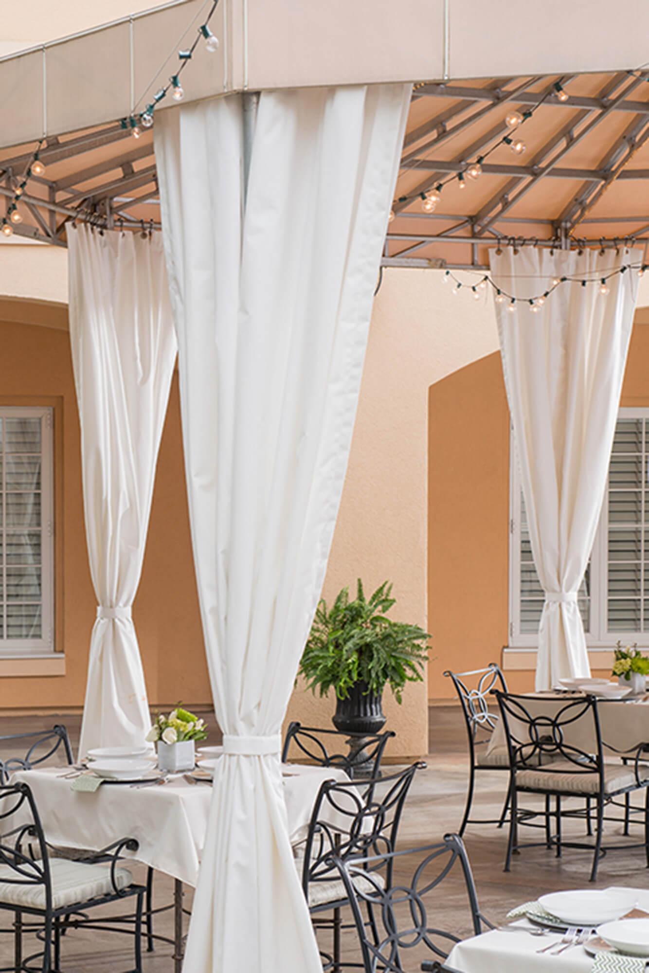 由 Sunbrella Clarity 织物制成的,固定过支架的遮阳蓬为餐馆露台遮阴