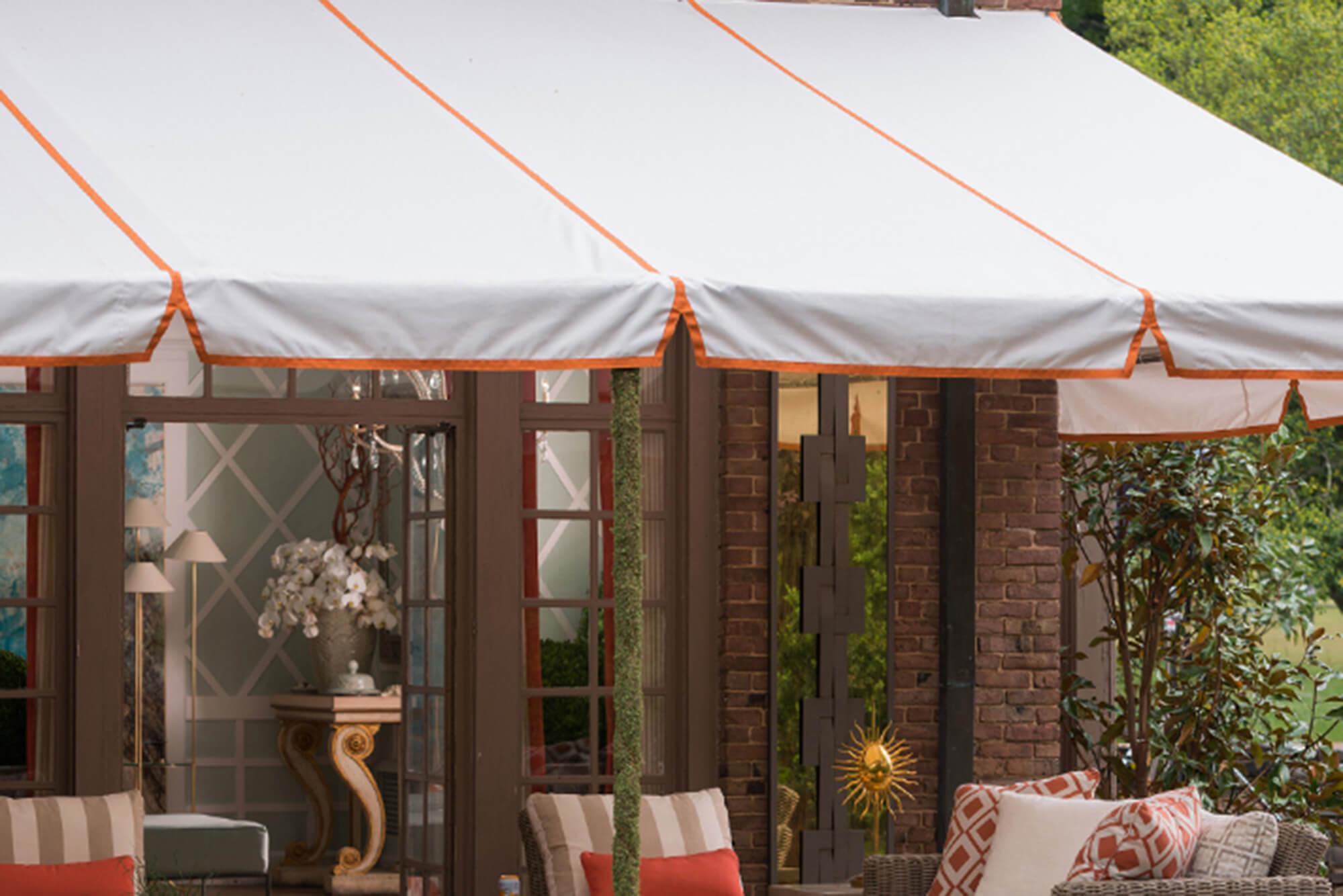 由白色 Sunbrella 织物制成的,并带有橘色饰物,经固定过支架的遮阳蓬为露台遮阴