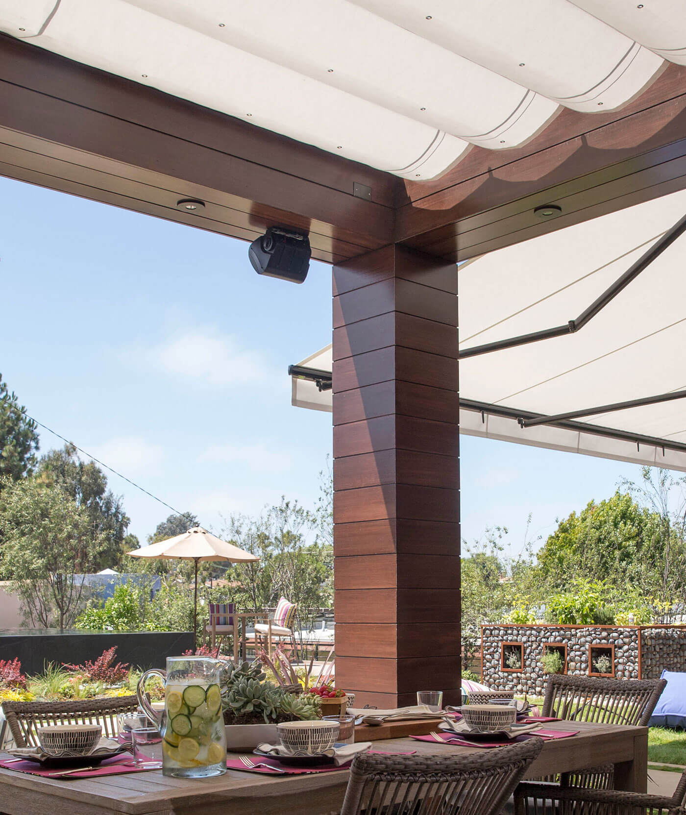 绿廊和由 Sunbrella 织物制成的可伸缩遮阳蓬为露台遮阴