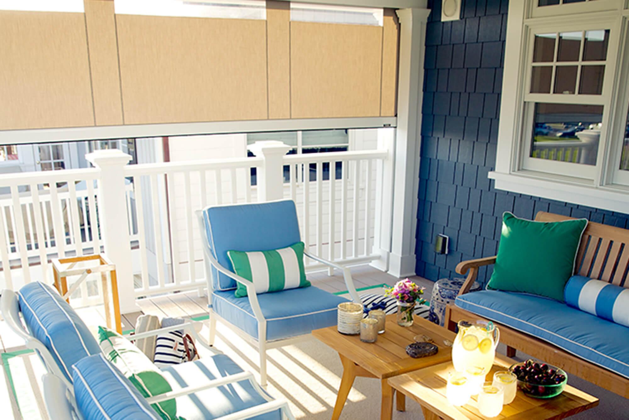 由米色 Sunbrella 织物制成的卷帘为露天平台遮阴,露台平台上还带有蓝色 Sunbrella 家具装饰织物