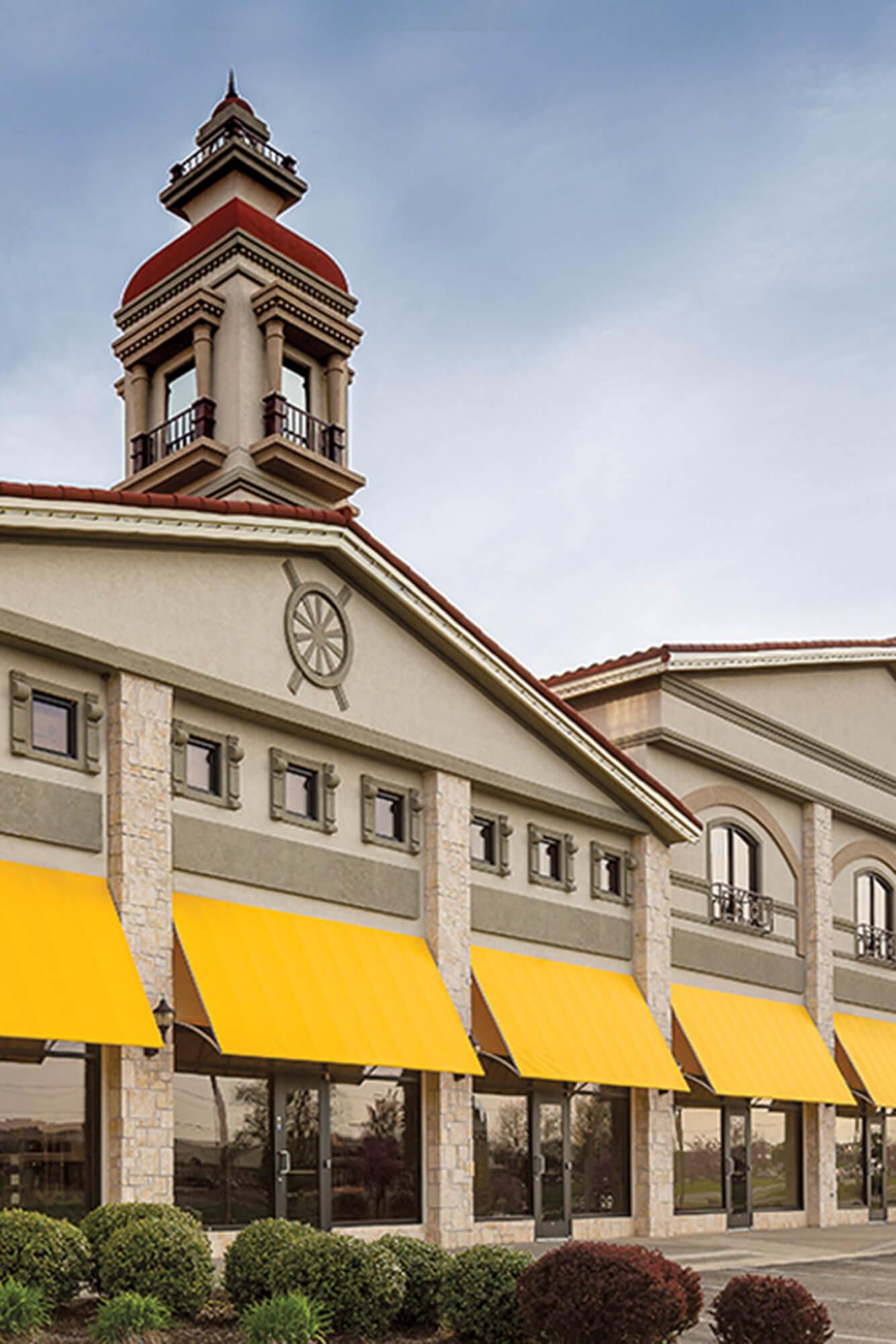 由黄色 Sunbrella Clarity 织物制成的固定过支架的遮阳蓬是购物中心的显著标志