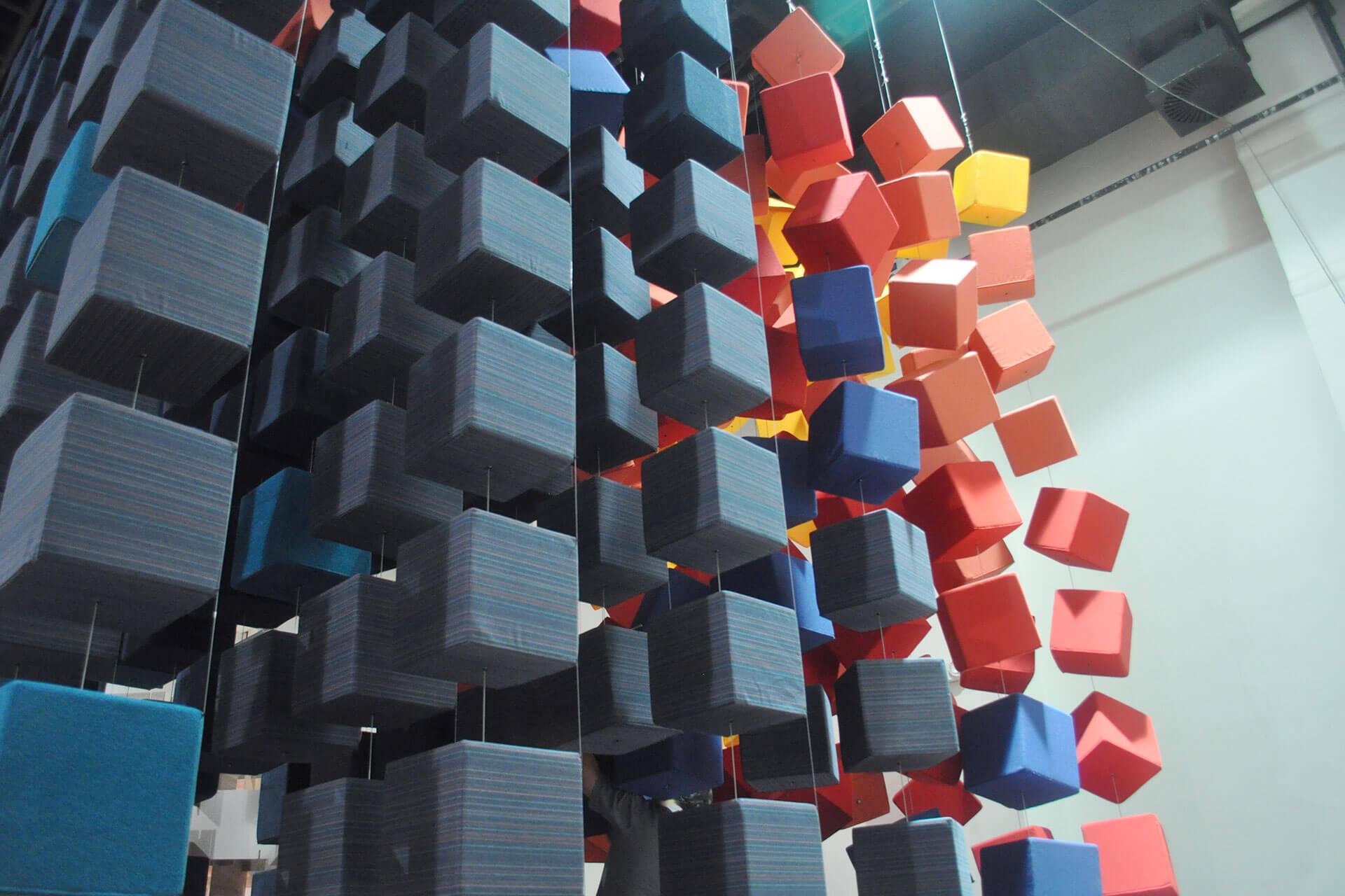 以蓝红双色 Sunbrella 布料制作的立方体,悬浮于新加坡 InDesign 展 Sunbrella Spectrum 艺术装置上方。