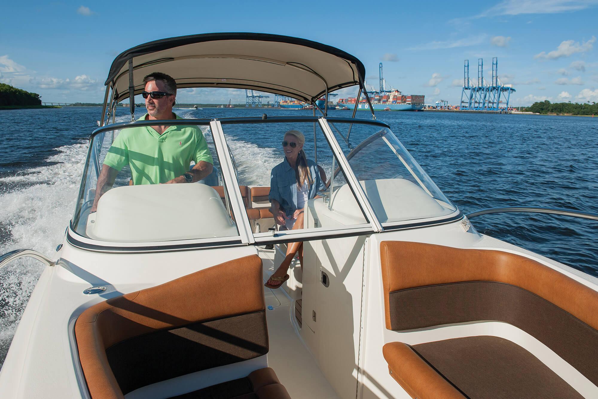 汽船上,一对夫妇在 Sunbrella Supreme 遮阳篷下休闲放松,船首还有棕色靠垫