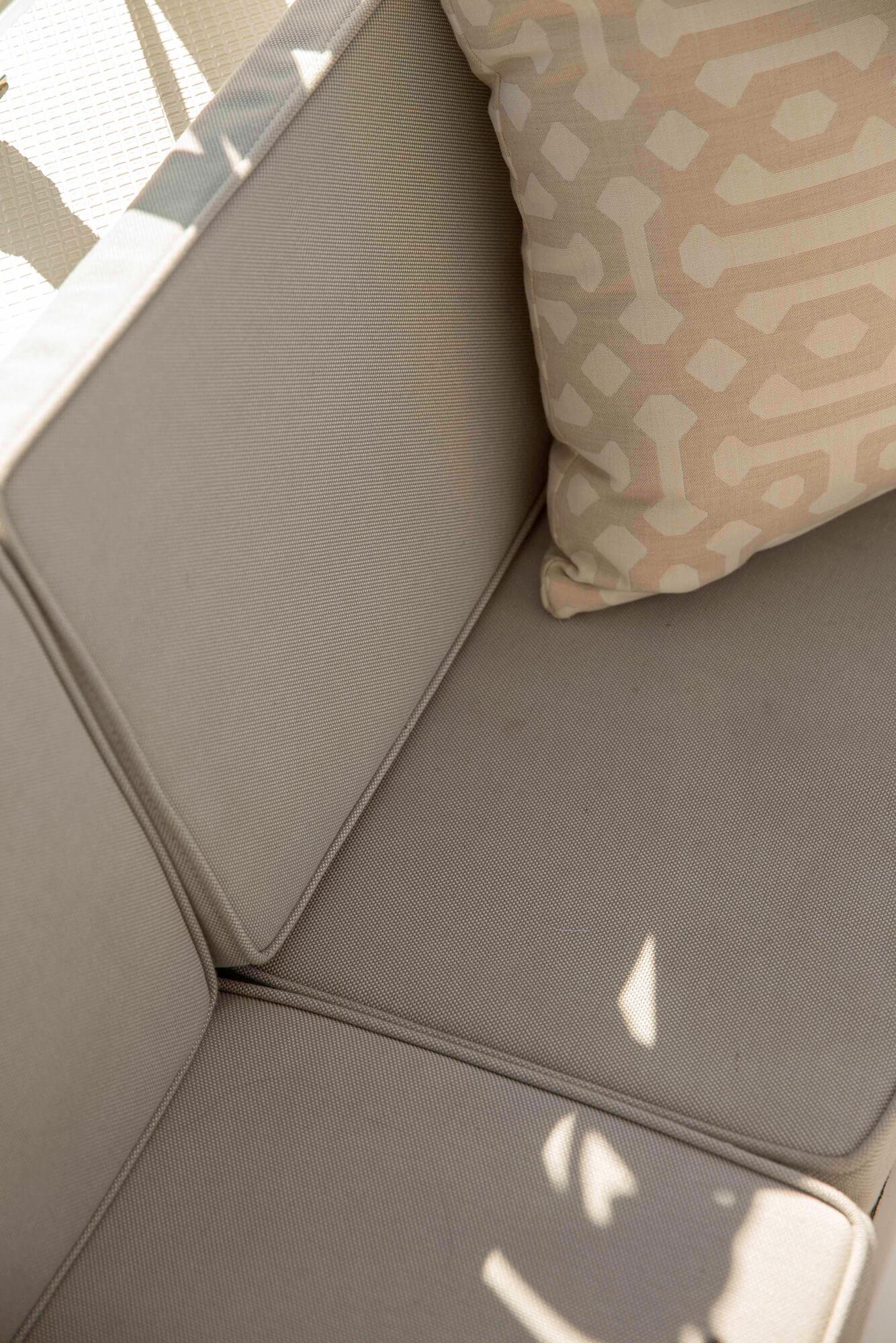 船座上的褐色坐垫,以及 Sunbrella Fretwork Flax 织物制成的精美枕头