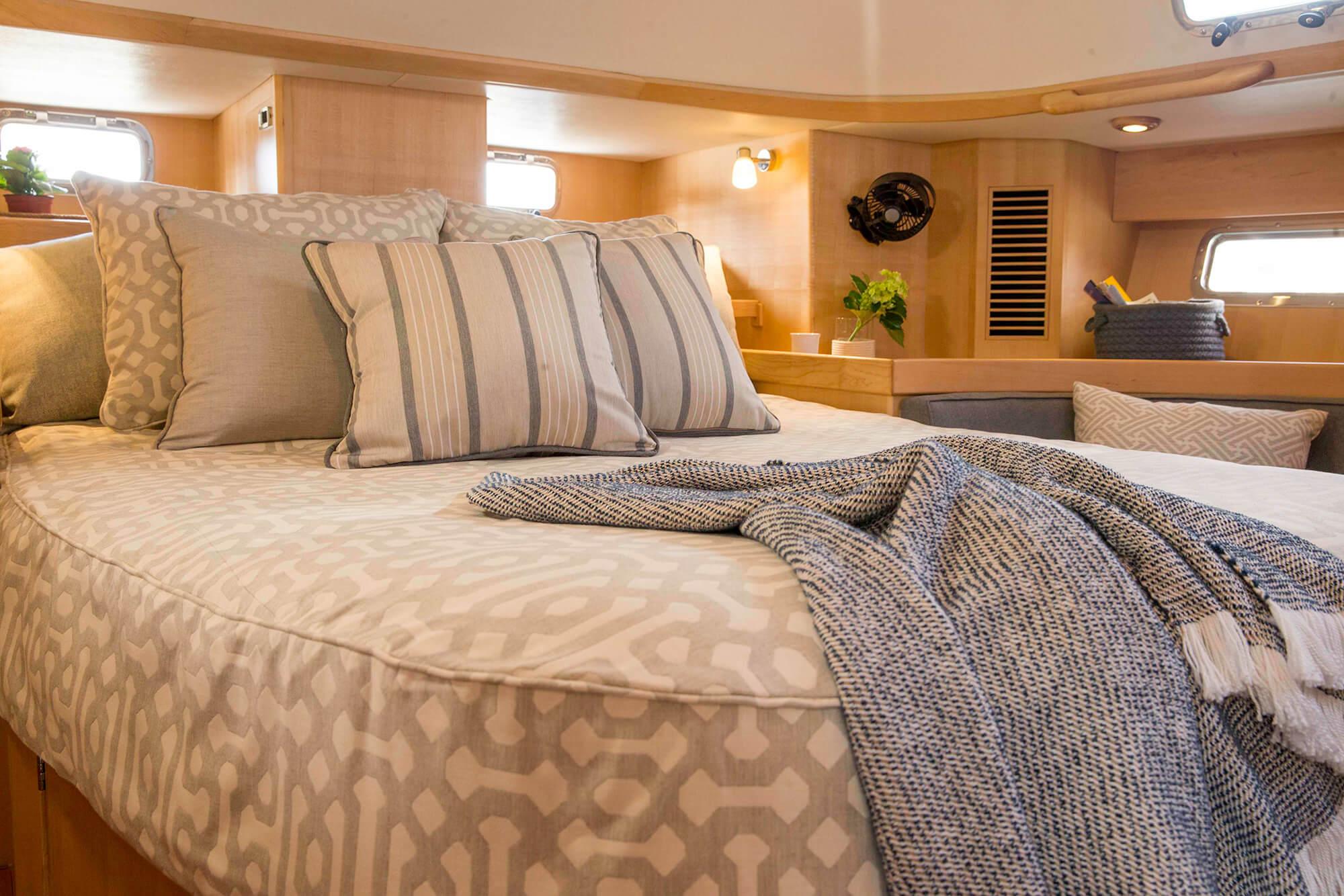 帆船上的床上,盖着 Sunbrella Fretwork Pewter 家纺用品和格调一致的抱枕