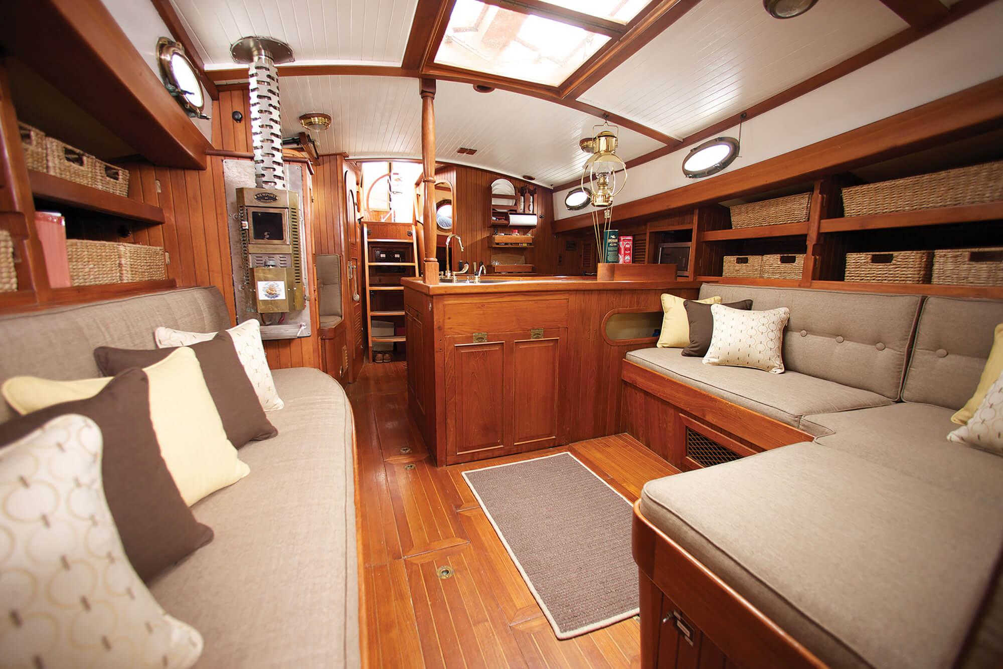 帆船舱内,棕黄色调下散落着 Sunbrella 织物制成的坐垫与枕头