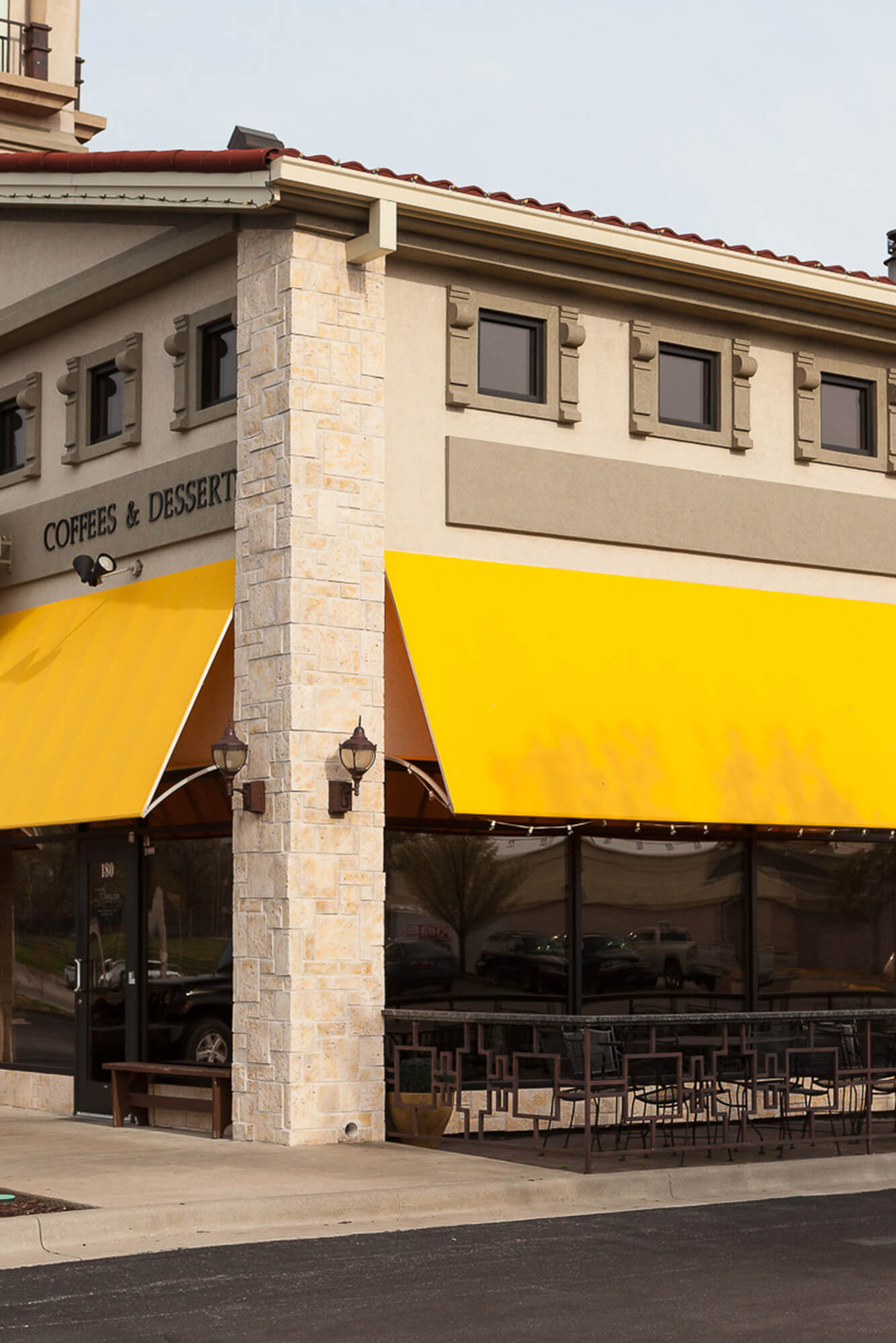 Yellow fixed frame awning made with Sunbrella Clarity fabric on a storefront
