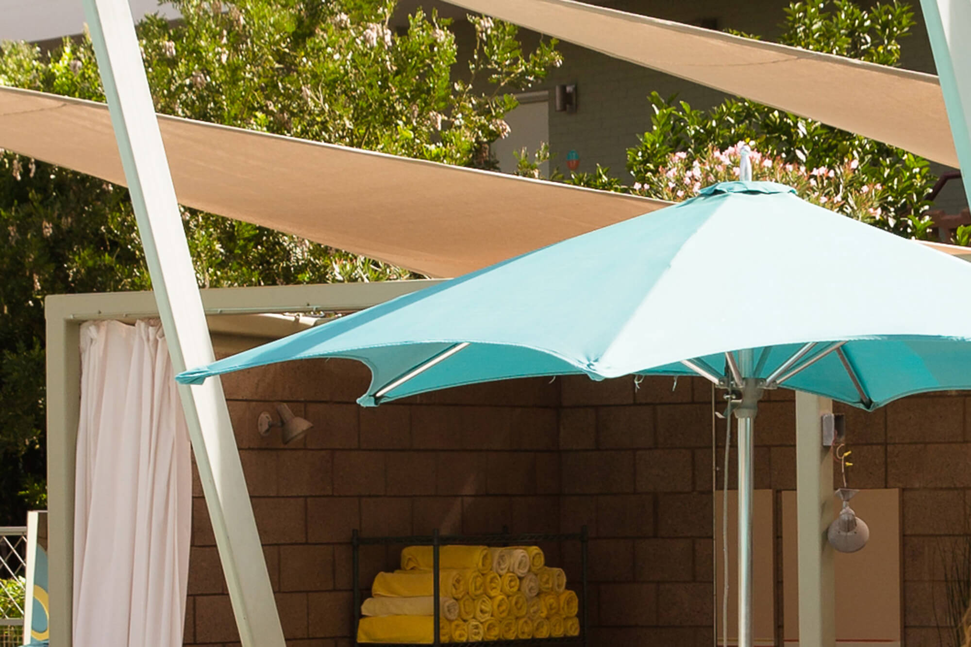 Umbrella with teal Sunbrella fabric poolside at a hotel