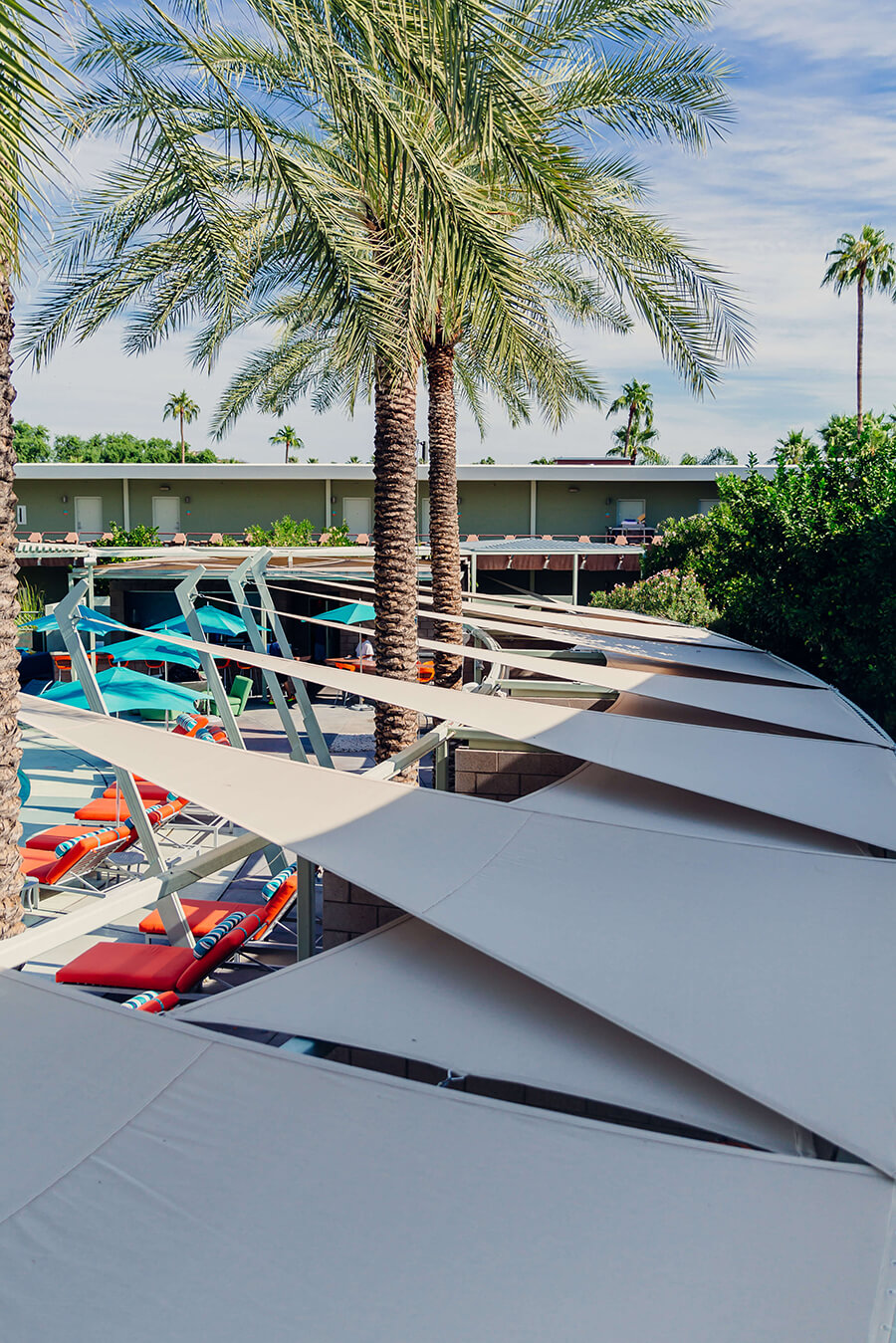 Shade sail with beige Sunbrella Contour fabric installed at hotel pool with palm trees in background
