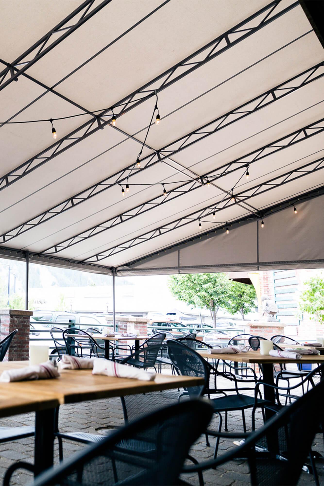 饭店露台上的褐色 Sunbrella 固定框架遮阳篷