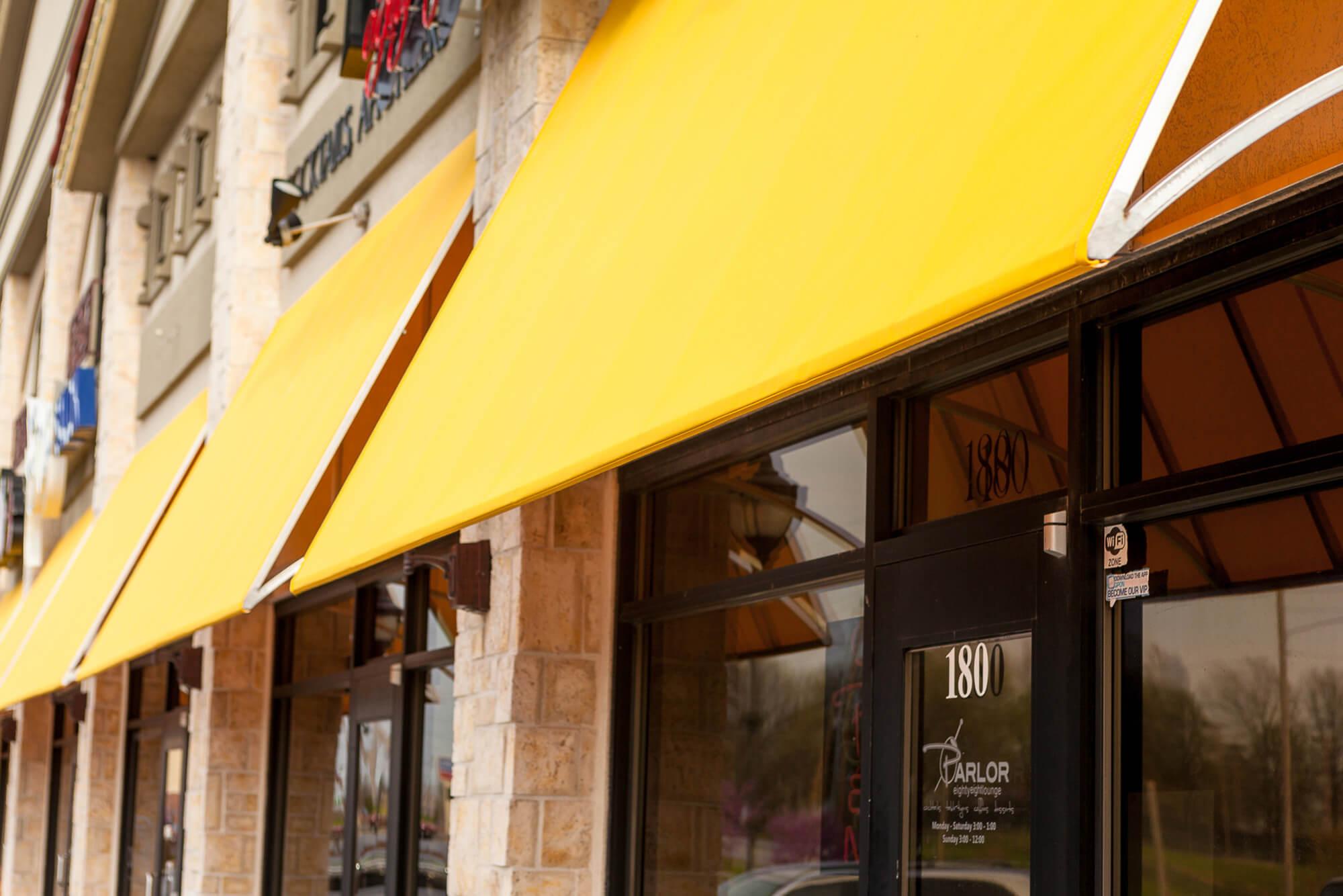 店门前的黄色 Sunbrella 织物固定框架遮阳篷