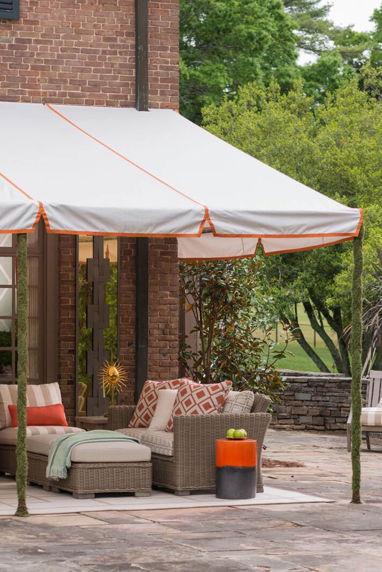 Patio coved with a fixed frame awning with white Sunbrella fabric and orange detailing
