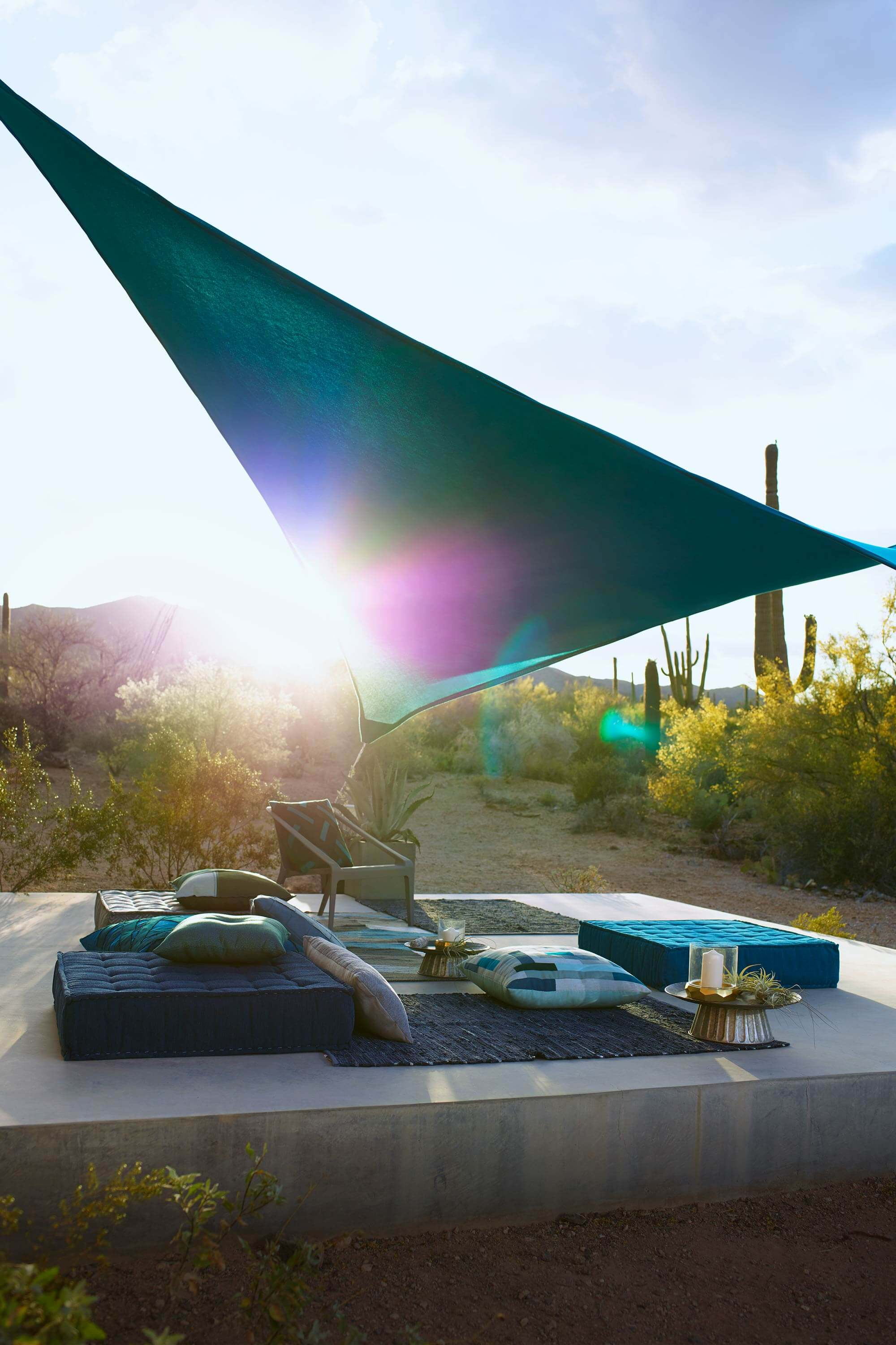 Outdoor seating of floor pillows covered with shade sail made using teal Sunbrella Contour fabric