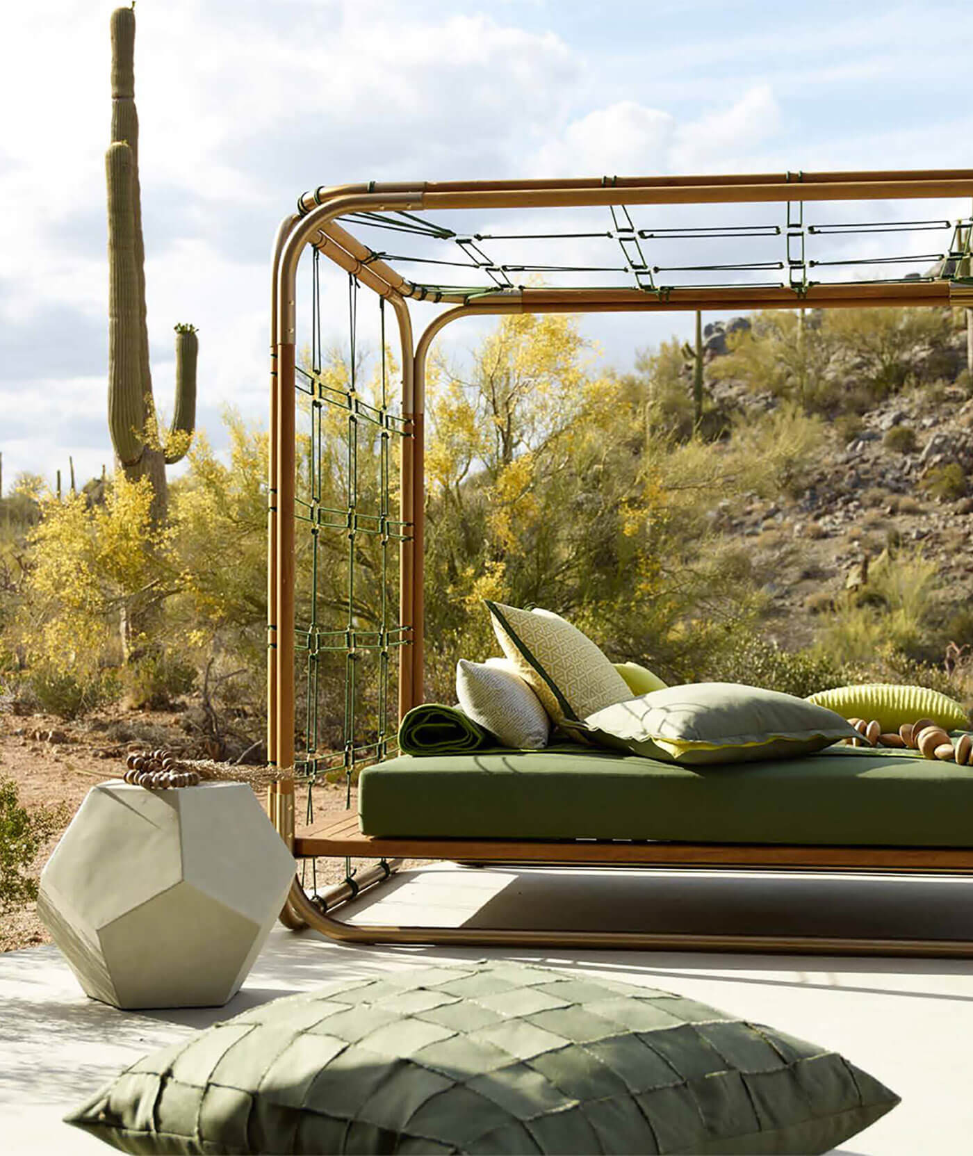 Daybed upholstered with green fabrics on patio with many decorative throw pillows