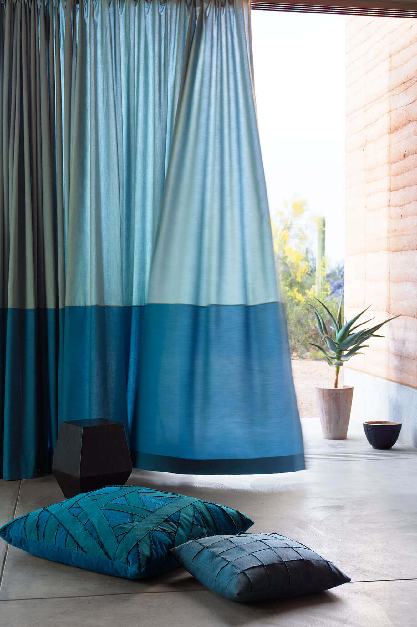 Blue drapery flows in the wind with decorative pillows on the floor