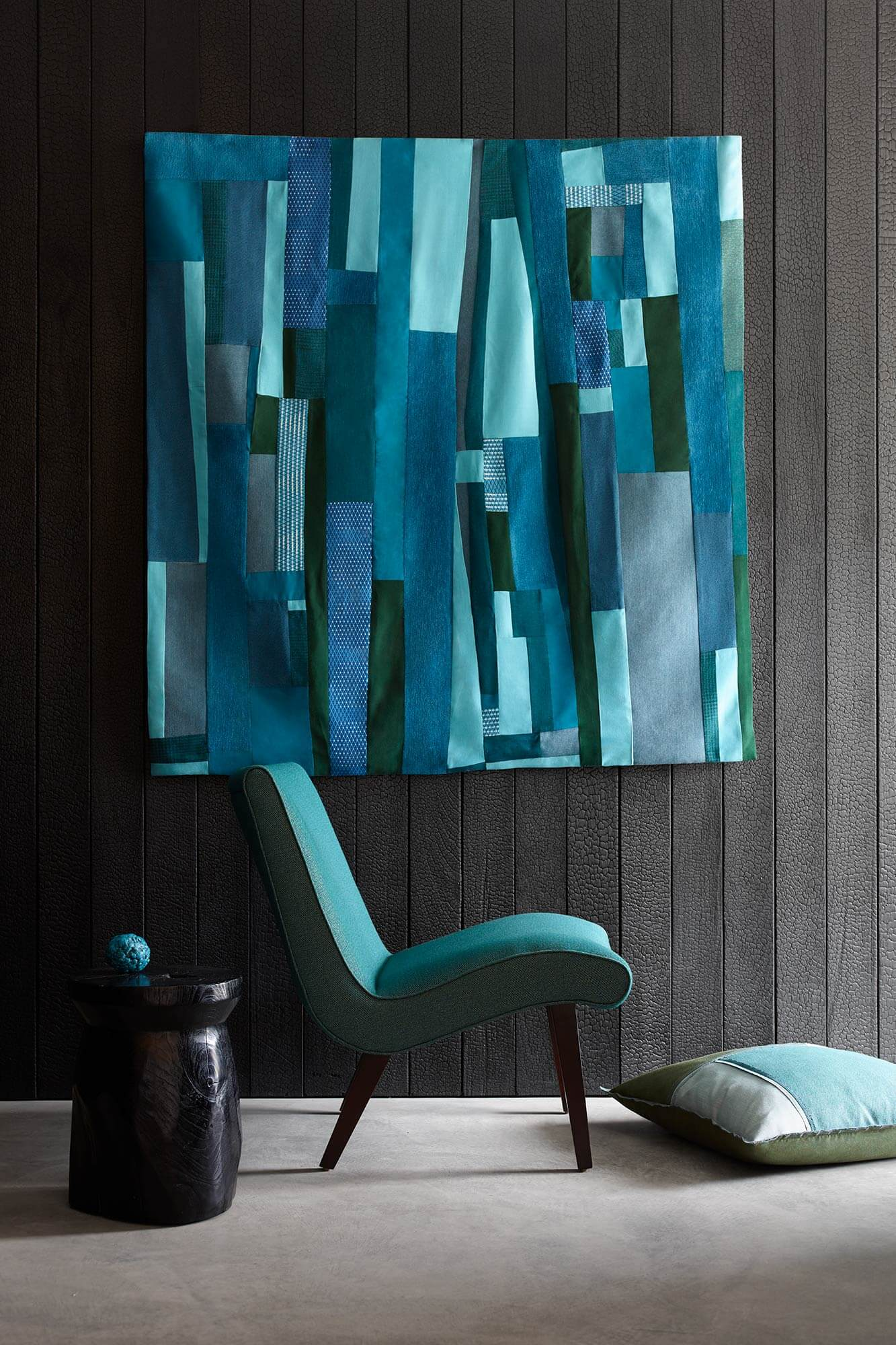 Teal upholstered armless chair with wall hanging featuring blue and green Sunbrella upholstery fabrics