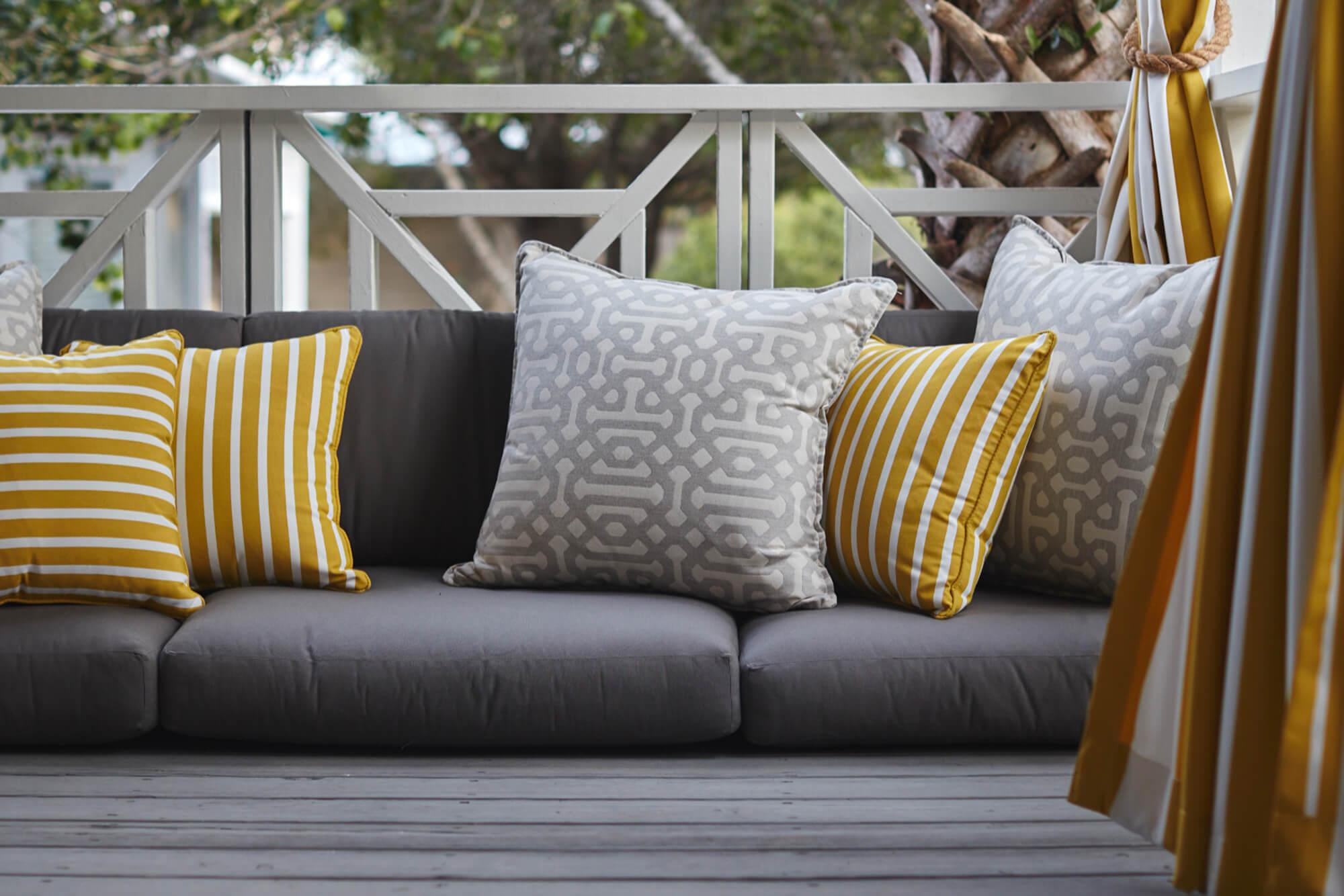 黄灰装饰的抱枕与黄色挂帘的灰色户外坐垫