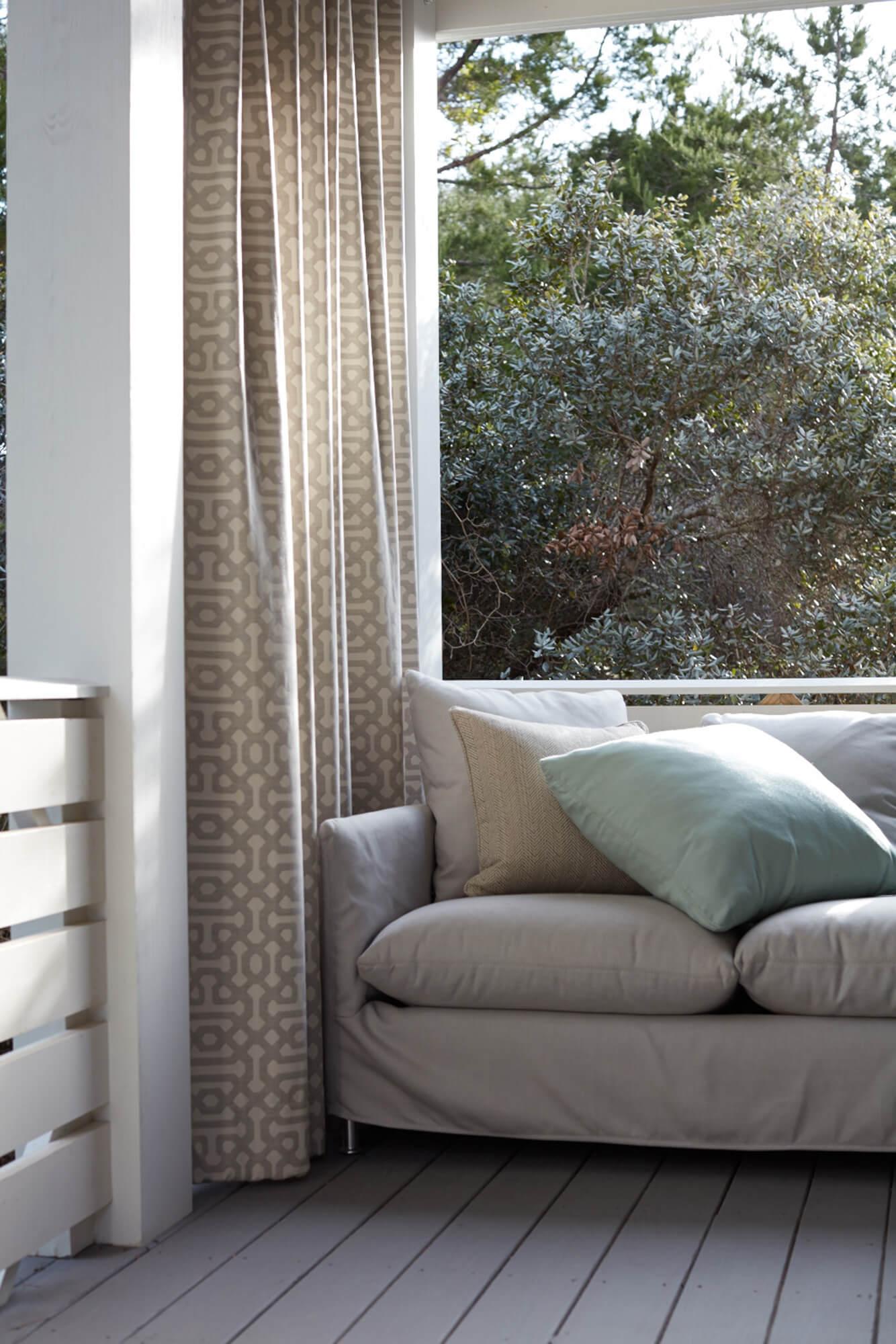 Sunbrella Fretwork Pewter 户外挂帘为放着精美抱枕的白色沙发提供遮挡
