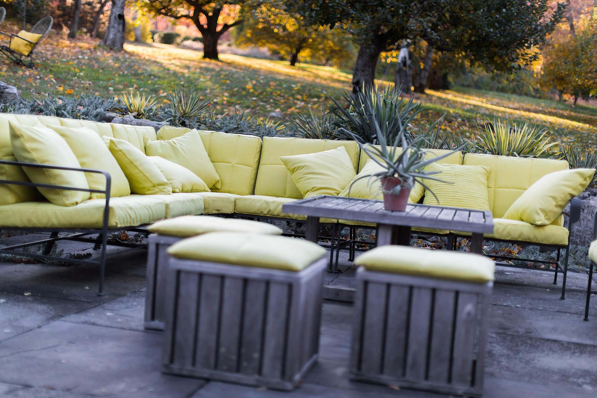 露台沙发上,采用绿色 Sunbrella 织物制成的坐垫