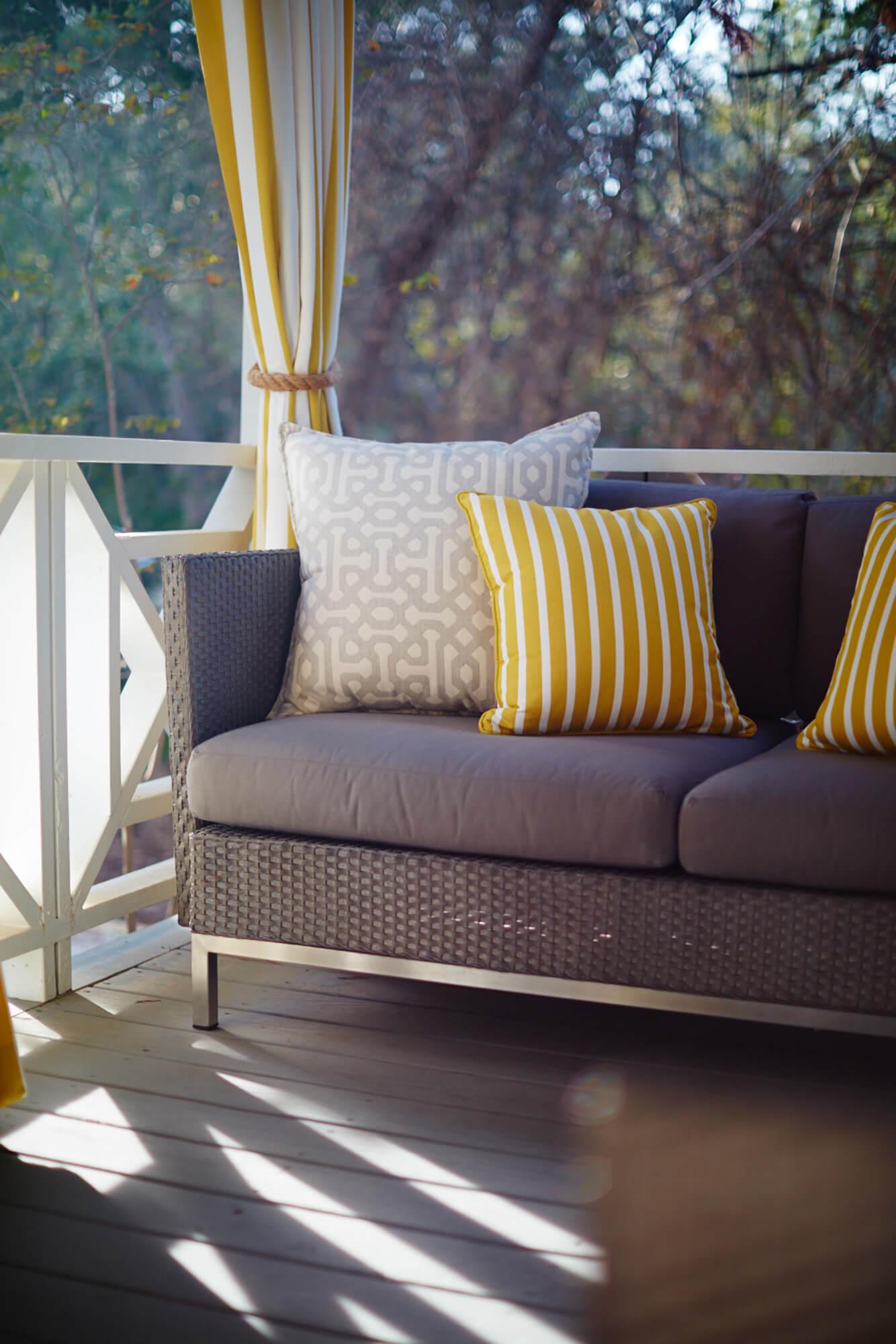 黄灰色抱枕与黄白条纹挂帘的户外沙发