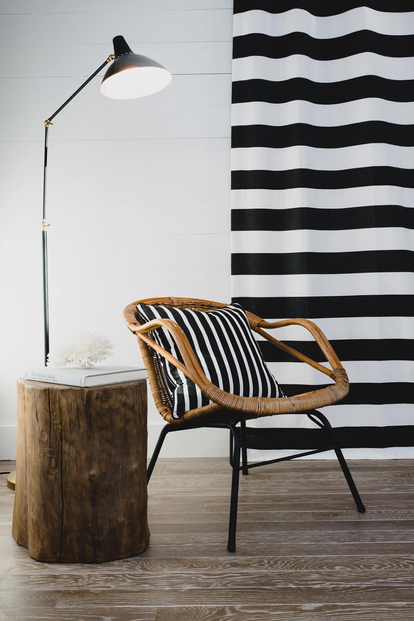 卧室坐椅上,Sunbrella 织物黑白条纹抱枕,与黑白条纹的挂帘背景融为一体